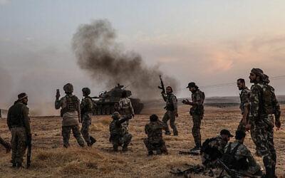 Des soldats turcs et des combattants syriens soutenus par la Turquie se rassemblent à la périphérie nord de la ville syrienne de Manbij, près de la frontière turque, le 14 octobre 2019, alors que la Turquie et ses alliés poursuivent leur attaque contre les villes frontalières kurdes du nord-est du pays. (Zein Al RIFAI / AFP)