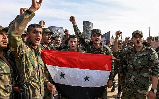 Les soldats du gouvernement syrien scandent des slogans lors d'une photo de groupe avec des portraits du président Bashar al-Assad près de Manbij, au nord de la province d'Alep, le 15 octobre 2019 (Crédit : - / AFP)