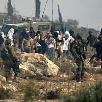 Photo d'illustration : Les soldats israéliens regardent des habitants d'implantation masqués jeter des pierres à des manifestants palestiniens (non-visibles sur la photo) pendant une manifestation contre la construction d'un avant-poste israélien aux abords du village de Turmusaya et de l'implantation de Shilo, au nord de Ramallah, en Cisjordanie, le 17 octobre 2019 (Crédit : JAAFAR ASHTIYEH / AFP)