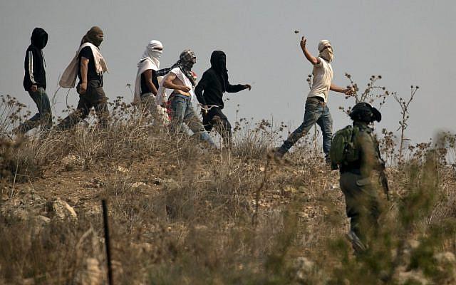 Illustration : les soldats israéliens regardent des habitants d'implantation masqués jeter des pierres à des manifestants palestiniens (non visibles sur la photo) pendant une manifestation contre la construction d'un avant-poste israélien aux abords du village de Turmusaya et de l'implantation de Shilo, au nord de Ramallah, en Cisjordanie, le 17 octobre 2019 (Crédit : JAAFAR ASHTIYEH / AFP)