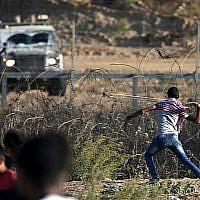 Illustration : Un Palestinien armé d'une fronde fjette des pierres aux forces israéliennes durant une émeute le long de la frontière avec Israël, à l'est de Bureij, dans le centre de la bande de Gaza, le 18 octobre 2019 (Crédit : Mahmud Hams/AFP)