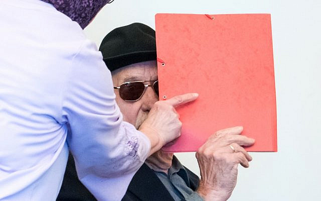 L'ancien gardien SS Bruno Dey, 93 ans, couvre son visage dans le tribunal pendant son procès à Hamburg, le 21 octobre 2019. (Crédit : Daniel Bockwoldt / POOL / AFP