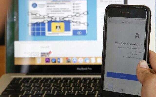 """Une photo prise le 23 octobre 2019 montre un Palestinien tenant un téléphone portable et affichant le message """"ce site n'est pas accessible"""" dans un bureau de la ville d'Hébron en Cisjordanie, suite à la décision d'un tribunal de Ramallah de bloquer l'accès à des dizaines de sites. (HAZEM BADER / AFP)"""