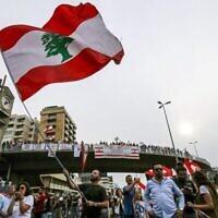 Un homme brandit un drapeau du Liban durant une manifestation sur l'autoroute qui relie Beyrouth à Tripoli, pendant des manifestations contre l'augmentation des impôts et la corruption au sein du gouvernement, le 26 octobre 2019. (Crédit : JOSEPH EID / AFP)