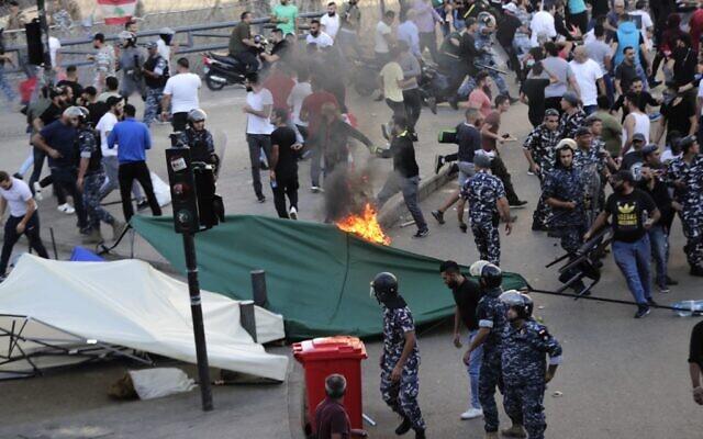 La police libanaise tente de séparer manifestants et contre-manifestants  durant un mouvement de protestation à Beyrouth, le 29 octobre 2019. (Crédit : ANWAR AMRO / AFP)