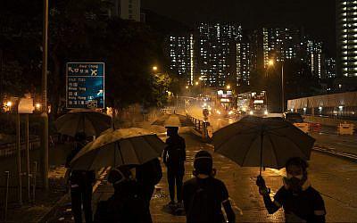 Les manifestants face aux gaz lacrymogènes à Hong Kong, le 6 octobre 2019 (Crédit : AP Photo/Felipe Dana)