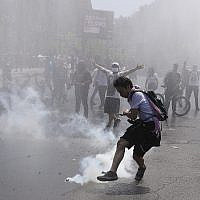 Un manifestant donne un coup de pied à une bouteille de gaz lacrymogène pendant des affrontements avec la police à Santiago, au Chili, le 20 octobre 2019 (Crédit : AP Photo/Esteban Felix)