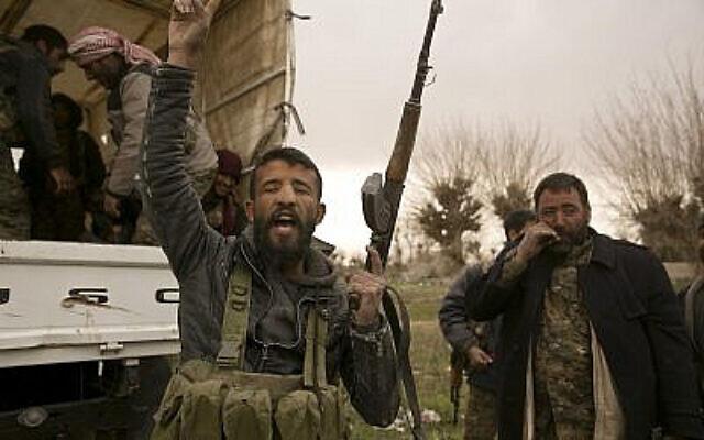 Un combattant des Forces démocratiques syriennes (FDS) soutenu par les États-Unis scande des slogans avant de se rendre en première ligne pour combattre les militants de l'État islamique dans leur dernier bastion de Baghouz, en Syrie, le 14 mars 2019. (AP Photo/Maya Alleruzzo)