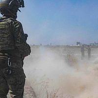 """Un soldat américain supervise des membres des Forces démocratiques syriennes alors qu'ils démolissent une fortification de combattants kurdes dans le cadre de ce qu'on appelle la """"zone de sécurité"""" près de la frontière turque, le 21 septembre 2019. (Armée américaine/Sergent d'état-major Andrew Goedl via AP)"""