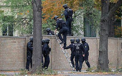 Des policiers traversent une rue proche du lieu d'une fusillade à Halle, dans l'est de l'Allemagne, le 9 octobre 2019 (Crédit : Sebastian Willnow / dpa / AFP) / Allemagne OUT
