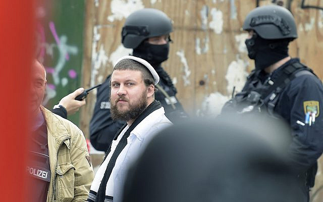 Un homme Juif entre des agents de police près du cimetière juif de Halle, à côté de la synagogue, le 9 octobre 2019. (Crédit : Jens Meyer/AP)