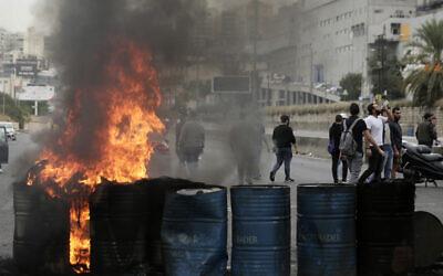 Des manifestants anti-gouvernements incendient des pneus pour bloquer une autoroute qui relie Beyriuth au nord du Liban à Zouk Mosbeh, le 28 octobre 2019. (Crédit : AP Photo/Hassan Ammar)