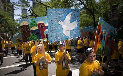 Un jeune garçon porte un panneau représentant une colombe de la paix avec d'autres élèves d'une école juive pendant le défilé Celebrate Israel à New York, le dimanche 1er juin 2014. (AP Photo/John Minchillo)