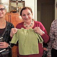 La docteure  Kristine Keren, au centre, avec une réplique de son pull vert de la Shoah fabriquée par la docteure Lea Stern, à gauche). L'époux de Keren, Marion, est à droite (Crédit : Julia Grossman)