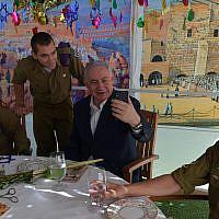De gauche à droite : Le caporal Aleksandra Vodenskov, le sergent Alexander Sachs, le Premier ministre Benjamin Netanyahu et le sergent Eddie Laufer idans la souccah du Premier ministre à Jérusalem, le 13 octobre 2019 (Crédit : Koby Gideon/GPO)