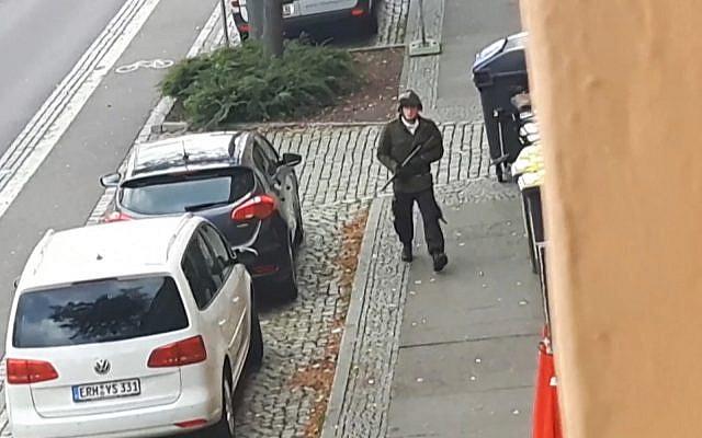 Un homme armé qui serait le tireur Stephan Balliet dans une rue de Halle, en Allemagne, pendant une fusillade aux abords d'une synagogue qui a fait deux morts dans la ville, le 9 octobre 2019 (Capture d'écran/Andreas Splett/ATV-Studio Halle/AFP)