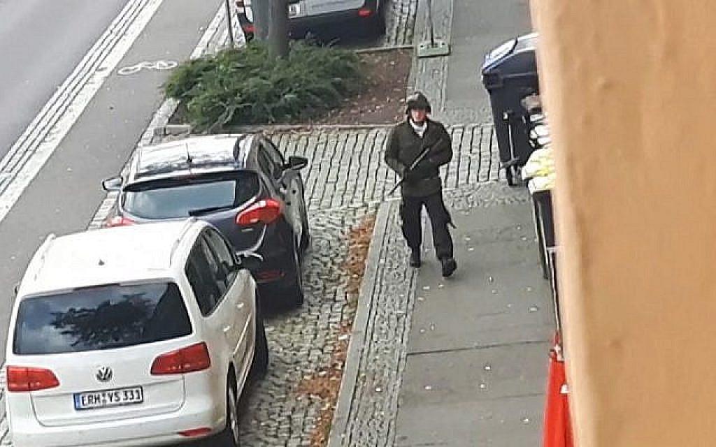 Un homme armé tire dans une rue de Halle, en Allemagne, après une fusillade devant une synagogue dans la même ville, faisant deux morts. (Crédit : capture d'écran / Andreas Splett / ATV-Studio Halle / AFP)