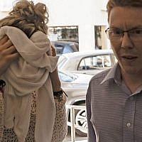 Une adolescent britannique (à gauche), accusé d'avoir prétendu avoir été violée par un groupe de touristes israéliens, couvrant son visage alors qu'elle arrive à son procès au tribunal de Famagusta à Paralimni à l'est de Chypre, le 2 octobre 2019. (Iakovos HATZISTAVROU/AFP)