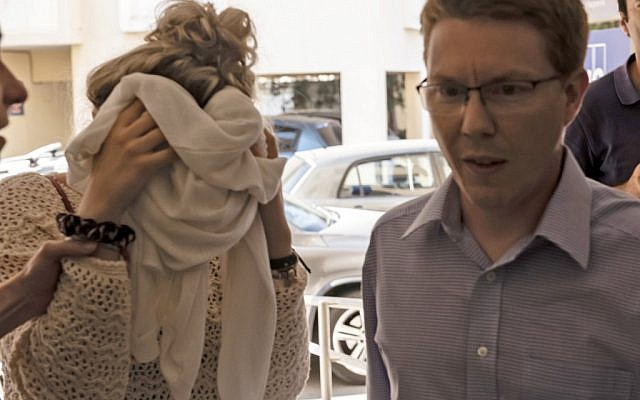 Une adolescente britannique (à gauche), accusé d'avoir prétendu avoir été violée par un groupe de touristes israéliens, couvrant son visage alors qu'elle arrive à son procès au tribunal de Famagusta à Paralimni à l'est de Chypre, le 2 octobre 2019. (Iakovos HATZISTAVROU/AFP)