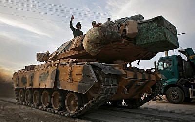 Des soldats turcs et des combattants syriens soutenus par la Turquie sur un tank de l'armée turque à proximité du village turc d'Akcakale le long de la frontière avec la Syrie, le 11 octobre 2019, alors qu'il se préparent à prendre part à un assaut mené par la Turquie dans le nord-est de la Syrie. (Bakr ALKASEM / AFP)