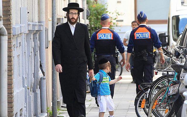 Un Juif orthodoxe et un enfant passent à côté de deux officiers de police à Antwerp, en Belgique, le 25 mai 2014. (AP Photo / Yves Logghe)