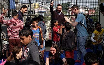Des participants au programme du grand rabbin britannique Ben Azzai jouent avec des orphelins indiens lors d'un voyage à Kolkata en décembre 2018. (Judah Ari Gross/Times of Israël)