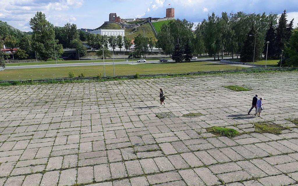 Des gens marchent dans un secteur où, il y a des décennies, se tenait un ancien cimetière juif, près d'un complexe sportif construit en  1971 par les Soviétiques abandonné et qui devrait être rénové, dans le centre de Vilnius, au mois de juillet 2019 (Crédit :  Raphael Ahren/TOI)