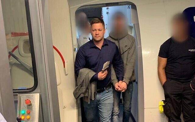 L'un des deux suspects (au centre) d'un meurtre à Petah Tivka, extradé depuis la Russie et arrêté à l'atterrissage en Israël, le 31 octobre 2019. (Crédit : police israélienne)