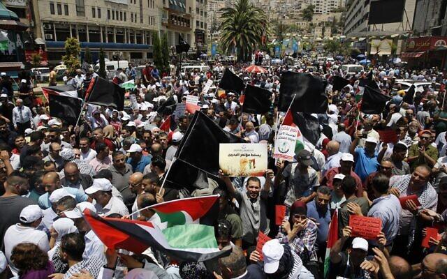 Des manifestants palestiniens brandissent des banderoles et des drapeaux nationaux lors d'une manifestation contre la conférence économique du Moyen Orient parrainée par les États-Unis qui s'est ouverte à Bahreïn, dans la ville de Naplouse, en Cisjordanie, le 25 juin 2019. (Jaafar Ashtiyeh/AFP)