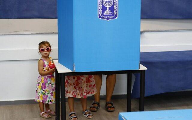 Des enfants israéliens accompagnent leur père lors des élections parlementaires dans un bureau de vote de Rosh Haayin, le 17 septembre 2019 (Crédit : Jack GUEZ / AFP)