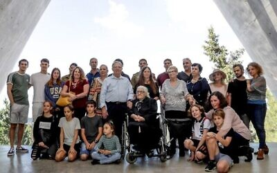 Melpomeni Dina (C), Juste parmi les Nations lors de la Seconde Guerre mondiale, pose pour une photo de groupe avec les survivants de la Shoah Yossi Mor (Cg et sa soeur Sarah Yanai (Cd), qu'elle a aidé à sauver en 1943, ainsi que leurs descendants dans la Salle des noms au Mémorial de l'Holocauste Yad Vashem à Jérusalem, le 3 novembre 2019. (Emmanuel DUNAND / AFP)