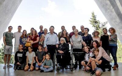 Melpomeni Dina (C), Juste parmi les Nations lors de la Seconde Guerre mondiale, pose pour une photo de groupe avec les survivants de la Shoah Yossi Mor (Cg et sa soeur Sarah Yanai (Cd), qu'elle a aidé à sauver en 1943, ainsi que leurs descendants dans la Salle des noms au Mémorial de l'Holocauste Yad Vashem à Jérusalem, le 3 novembre 2019. (Emmanuel DUNAND / AFP)