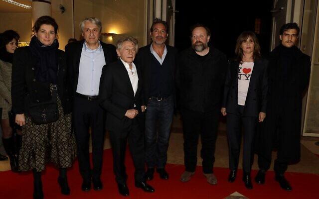 """Le réalisateur franco-polonais Roman Polanski (3g), accompagné du producteur Alain Goldman (2g), de l'acteur français Jean Dujardin (C), de l'acteur français Gregory Gadebois (3d), de l'acteur français Louis Garrel (à droite) et de l'actrice française Emmanuelle Seigner (2d) arrivent à l'avant-première de son dernier film """"J'accuse"""" à Paris, le 4 novembre 2019. (Crédit : Thomas SAMSON / AFP)"""
