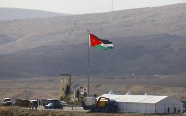 Photo prise du côté israélien de la frontière: des soldats jordaniens plantent le drapeau national avant une cérémonie dans la vallée du Jourdain, à Naharayim, le 10 novembre 2019. (Crédit : MENAHEM KAHANA / AFP)