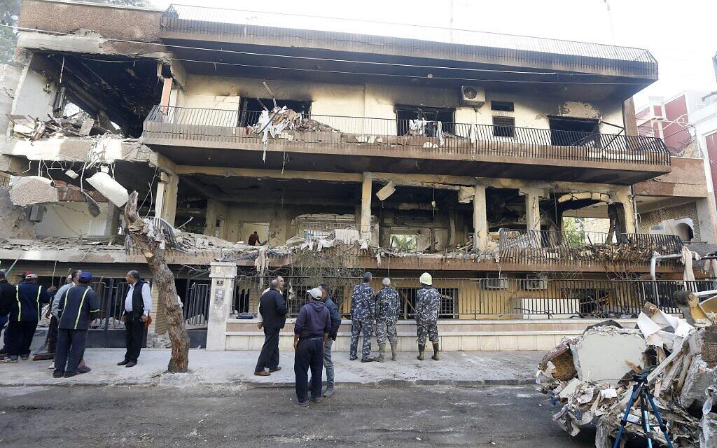 Les forces de sécurité et des employés de la mairie devant une immeuble visé par une frappe en Syrie, le 12 novembre 2019. (Crédit : LOUAI BESHARA / AFP)