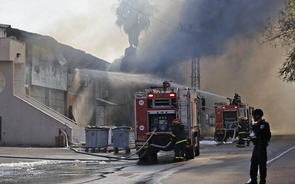 Des pompiers israéliens tentent de maîtriser un incendie qui ravage un entrepôt à Sderot, après qu'une roquette tirée depuis Gaza a frappé le bâtiment, le 12 novembre 2019. (Crédit : Ahmad GHARABLI / AFP)
