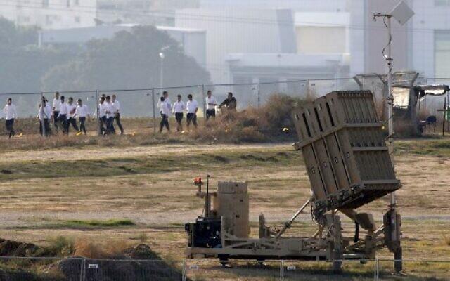 Des étudiants israéliens marchent devant une batterie du système de défense antimissiles du Dôme de fer, chargé d'intercepter et de détruire les roquettes à courte-portée et les obus d'artillerie dans la ville d'Ashdod, dans le sud d'Israël, près de la bande de Gaza, le 12 novembre 2019 (Crédit : JACK GUEZ / AFP)