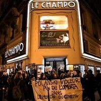 "Des manifestants brandissent des pancartes et autres lors de protestations contre le réalisateur franco-polonais Roman Polanski devant le cinéma ""Le Champo"" à Paris, le 12 novembre 2019. (Crédit: Christophe ARCHAMBAULT / AFP)"