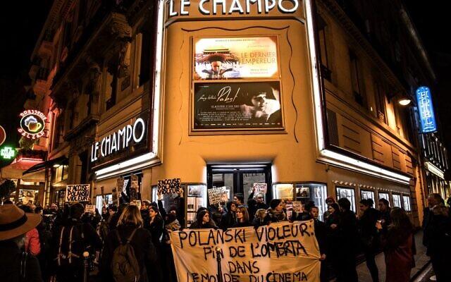 """Des manifestants brandissent des pancartes et autres lors de protestations contre le réalisateur franco-polonais Roman Polanski devant le cinéma """"Le Champo"""" à Paris, le 12 novembre 2019. (Crédit: Christophe ARCHAMBAULT / AFP)"""