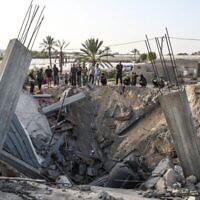 Des Palestiniens réunis autour des restes d'une maison détruite dans une frappe aérienne israélienne à Khan Younès, dans le sud de la bande de Gaza, le 13 novembre 2019 (Crédit :  SAID KHATIB / AFP)