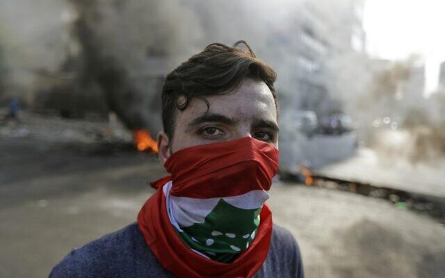 Un manifestant libanais se trouve devant des pneus et des débris en feu dans la zone de Jal el-Dib, dans la banlieue nord de la capitale libanaise de Beyrouth, le 13 novembre 2019.  (Photo par JOSEPH EID / AFP)