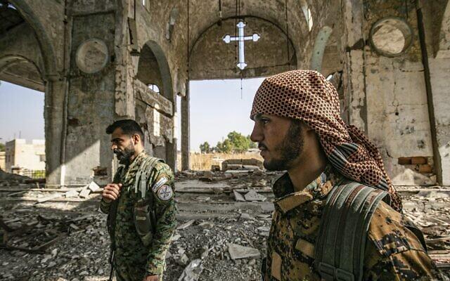 Des membres de la milice syrienne assyrienne des gardes du Khabour (MNK), affiliée aux Forces démocratiques syriennes (FDS), marchent dans les ruines de l'église assyrienne de la Vierge Marie, qui avait été détruite le 15 novembre 2019 dans le village de Tal Nasri, au sud de Tal Tamr (province du Hasakah, au nord-est du pays). (Crédit : Delil souleiman / AFP)