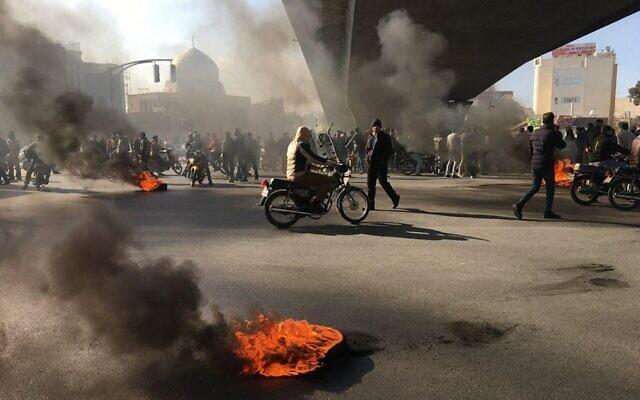 Des manifestants iraniens incendient des pneus pendant une manifestation contre la hausse des prix du carburant, à Ispahan, le 16 novembre 2019. (Crédit : AFP)
