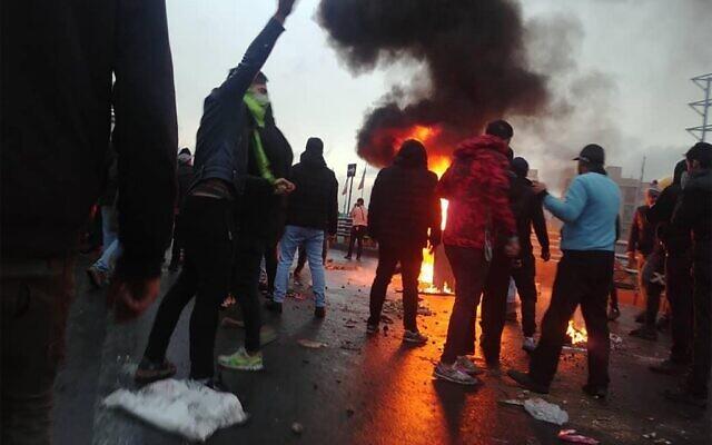 Des manifestants iraniens se rassemblent autour d'un feu lors d'une manifestation contre la hausse des prix de l'essence dans la capitale Téhéran, le 16 novembre 2019. (Crédit : AFP)