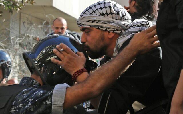 Un manifestant libanais embrasse le casque d'un policier près du Parlement, à Beyrouth, le 19 novembre 2019. (Crédit : Anwar AMRO/AFP)