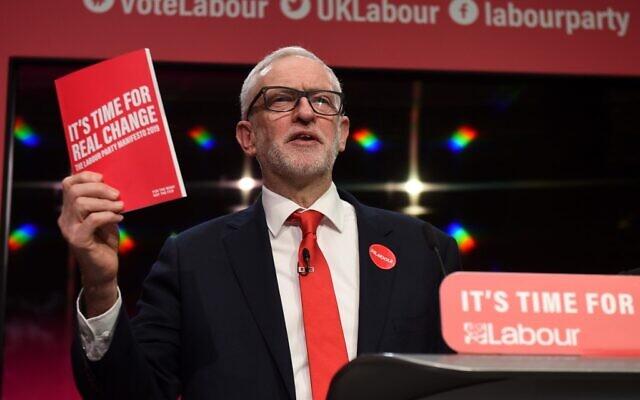 Le leader du parti britannique d'opposition du Labour Jeremy Corbyn tient une copie du programme du parti durant le lancement de ce manifeste de campagne électorale à  Birmingham, dans le nord-ouest de l'Angleterre, le 21 novembre 2019 (Crédit : Oli Scarff/AFP)