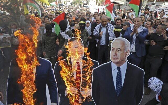 Des manifestants palestiniens brûlent des cartons à l'effigie Donald Trump, Mike Pompeo et Benjamin Netanahu, à Naplouse, le 26 novembre 2019. (Crédit : Jaafar ASHTIYEH / AFP)
