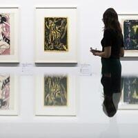 """Une visiteuse regarde les peintures """"Melancholisches Maedchen"""", à gauche, et Nackte Frau im Walde"""" du peintre allemand  Ernst Ludwig Kirchner, dans l'exposition 'Rapport de statut Gurlitt. Art dégénéré - confisqué et vendu' organisée au Kunstmuseum de Bern, en Suisse, le 1er novembre 2017 (Crédit : Peter Klaunzer/Keystone via AP)"""