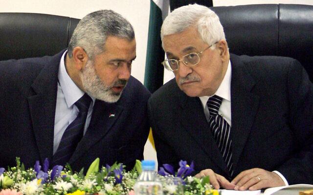 Le président de l'Autorité palestinienne Mahmoud Abbas (à droite) et le Premier ministre palestinien Ismail Haniyeh du Hamas (à gauche) à la tête de la première réunion du cabinet du nouveau gouvernement de coalition au bureau d'Abbas à Gaza, le 18 mars 2007. (AP Photo/Khalil Hamra, File)