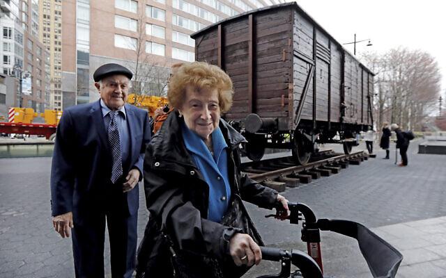 Les survivants de la Shoah Leon Kaner, 94 ans, et son épouse , Ray Kaner, 92 ans, devant un wagon plombé allemand comme ceux utilisés pour transporter les Juifs à  Auschwitz et dans les autres camps de la mort aux abords du  Museum of Jewish Heritage, à New York, le 31 mars 2019 (Crédit : AP Photo/Richard Drew)